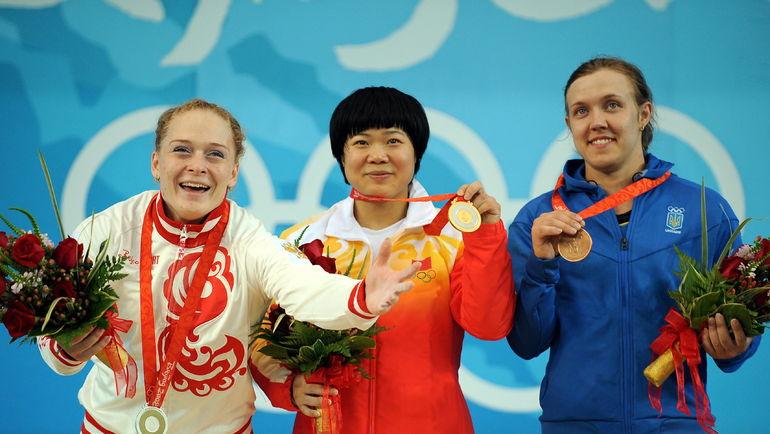 13 августа 2008 года. Пекин. Оксана СЛИВЕНКО (слева) с серебром Олимпийских игр. Вместо той медали Пекина россиянка получит золото после дисквалификации ЛЮ ЧУНЬХУНА (в центре). Справа - бронзовый призер, украинка Наталья ДАВЫДОВА. Фото REUTERS