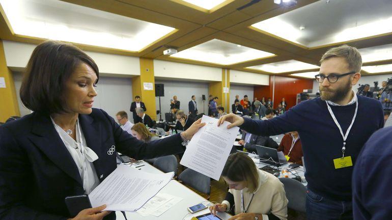 Медиа-офицер МОК Эммануэль МОРО раздает журналистам решение исполкома по России. Фото REUTERS