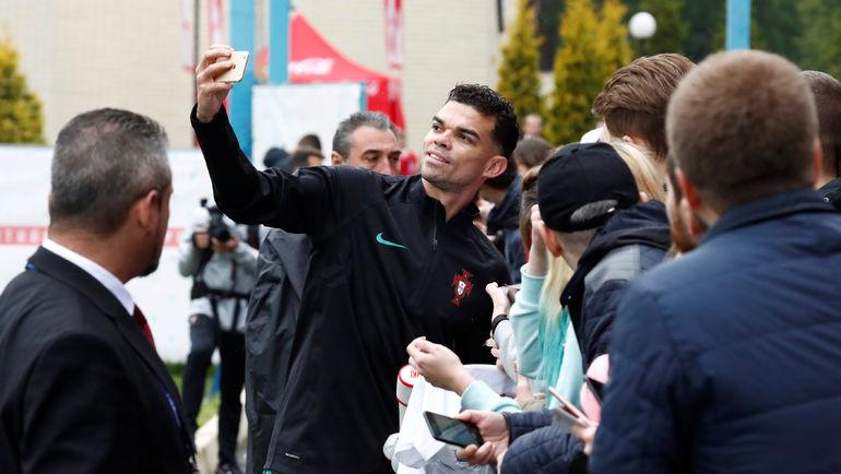 Воскресенье. Кратово. Защитник португальцев ПЕПЕ фотографируется с фанатами после тренировки. Фото REUTERS