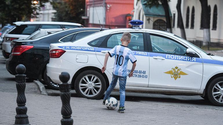 """Мальчик в форме Лионеля Месси играет возле полицейской машины. Фото Дарья ИСАЕВА , """"СЭ"""""""