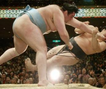 9 января 2006 года. Токио. КОККАЙ в результате силового теснения опрокидывает легендарного йокодзуну АСАШОРЮ. Фото AFP
