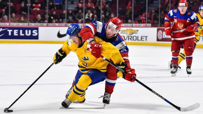 Михаил ВОРОБЬЕВ (в красном) в игре со Швецией. Фото AFP