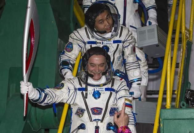 Сегодня. Байконур. Члены экипажа новой экспедиции на МКС с факелом Олимпиады-2014. Фото Reuters