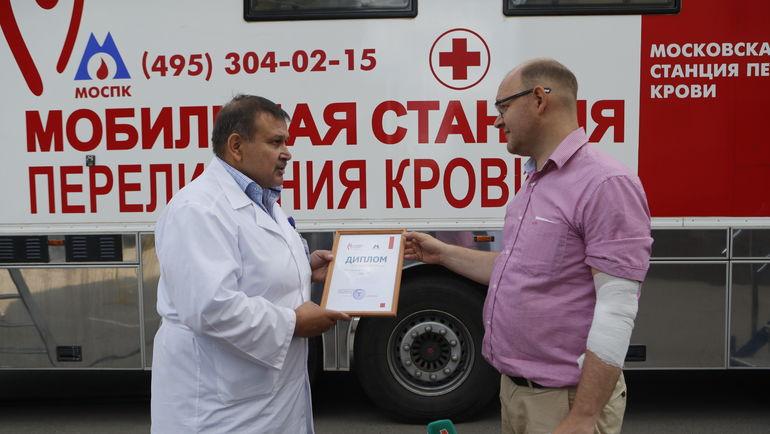 Илья ГЕРКУС (справа) получает от врача-трансфузиолога Сергея ДЕМИНА грамоту с благодарностью за участие в акции.