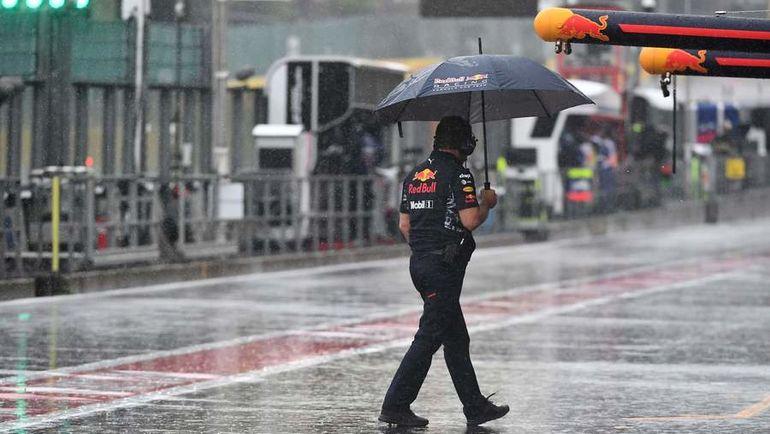 "Сотрудник команды ""Ред Булл"" во время дождя. Фото AFP"