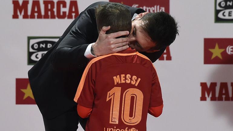 """Лионель МЕССИ благодарит маленького мальчика, вручившего ему приз """"Золотое сердце"""". Фото AFP"""