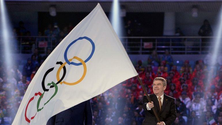 Президент МОК Томас БАХ с олимпийским флагом на Играх-2014 в Сочи. Фото REUTERS