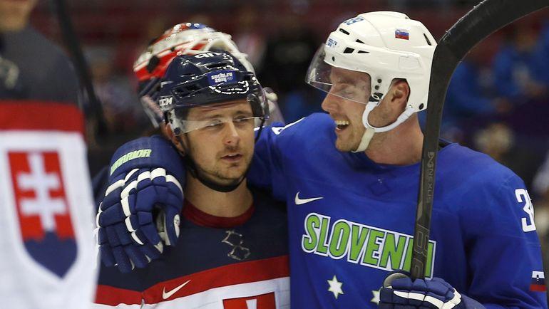 Словенец Ян МУРШАК со словаком Томашем ТАТАРОМ после матча олимпийского турнира в Сочи. Фото Reuters