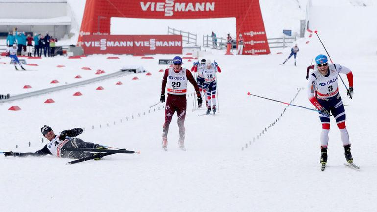 Суббота. Холменхоллен. Максим ВЫЛЕГЖАНИН (в центре), Мартин Йонсруд СУНДБЮ (справа) и Дарио КОЛОНЬЯ (на снегу) на финише масс-старта на 50 км. Фото Reuters