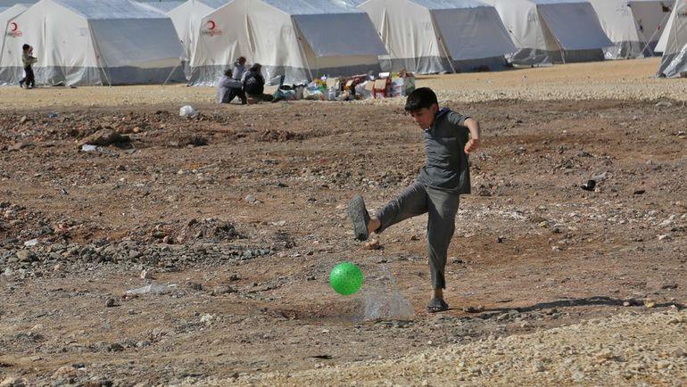 Сирийский мальчик играет в мяч в лагере для беженцев. Фото AFP