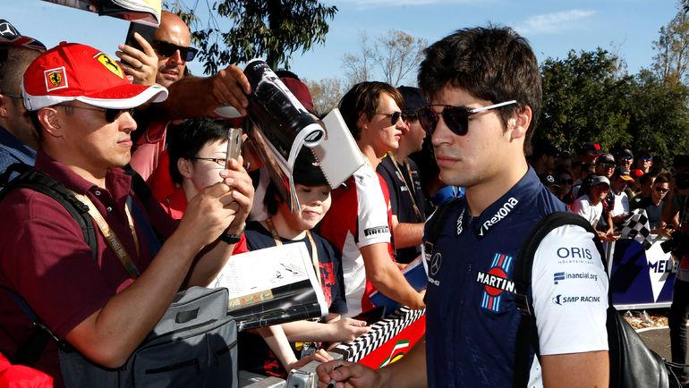 23 марта. Мельбурн. Канадский автогонщик Лэнс СТРОЛЛ (справа) с фанатами. Фото Reuters
