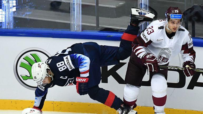 Четверг. Хернинг. США - Латвия - 3:2 ОТ. Теодорс БЛЮГЕРС (справа) проводит силовой прием против Патрика КЕЙНА. Фото AFP