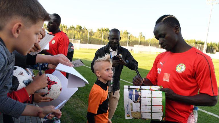 15 июня. Калуга. Нападающий сборной Сенегала Садио МАНЕ после тренировки подписывает журнал юному болельщику. Фото AFP