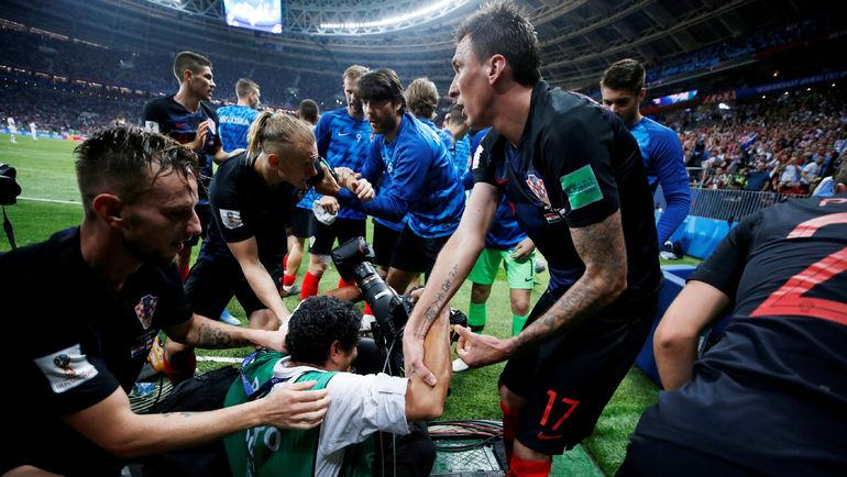 Иван РАКИТИЧ, Домагой ВИДА и Марио МАНДЖУКИЧ помогают Юрию КОРТЕСУ подняться. Фото Reuters