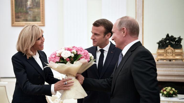Владимир Путин перед финалом ЧМ-2018 дарит букет цветов супруге Эманюэля Макрона. Фото REUTERS