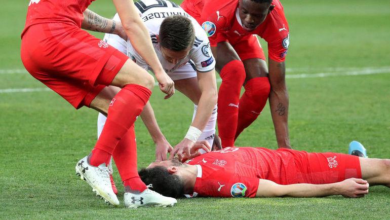 23 марта. Тбилиси. Грузия - Швейцария - 0:2. Джано Ананидзе помогает Фабиану Шеру после столкновения с Джемалом Табидзе. Фото Reuters