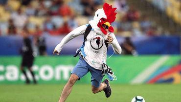 Фанат в маске петуха в матче Кубка Америки. Его остановил чилиец Хара