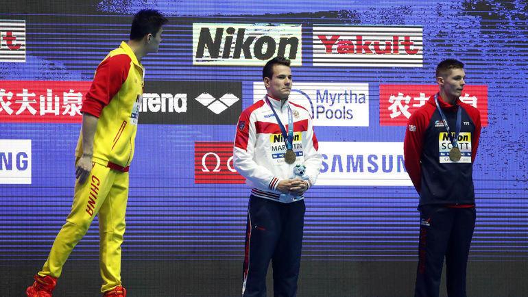 Сунь Ян (слева) кричит на Данкана Скотта (справа, в центре - Мартин Малютин) во время награждения. Фото REUTERS