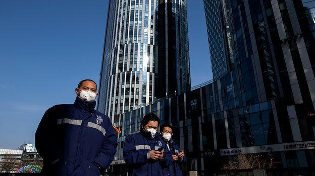 Сотрудники эпидемиологической службы наулице столицы Китая. Фото AFP