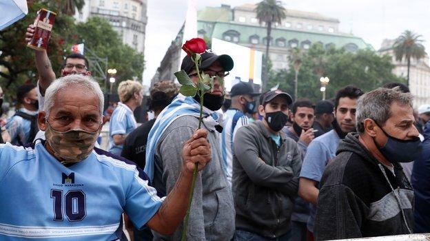 Фанаты несут цветы на прощание с Марадоной. Фото AFP