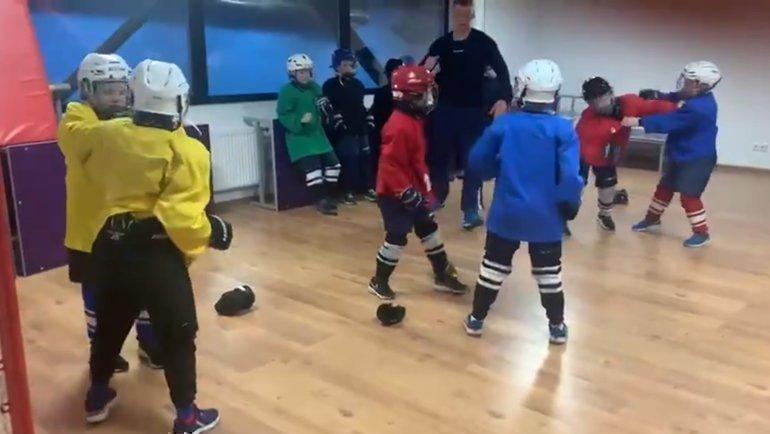 Детский тренер обучает юных хоккеистов дракам.