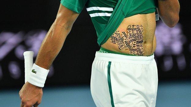 Издалека может показаться, что это татуировка, нонет. Новак использовал специальные узорчатые пластыри, чтобы закрыть поврежденную область тела. Фото AFP