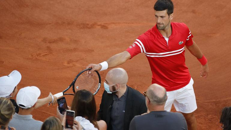Новак Джокович делает подарок болельщику. Фото Reuters