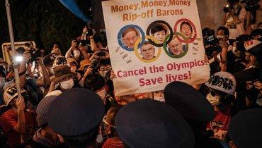23июля. Токио. Полицейские останавливают протестующих против проведения Олимпиады вЯпонии.