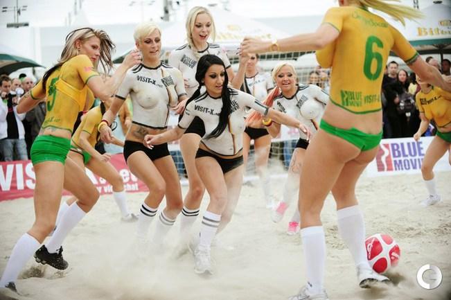 Иногда девушки играют в футбол и без верхней части купальника. .