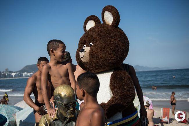 Олимпийский Мишка гуляет по пляжу в Рио-де-Жанейро