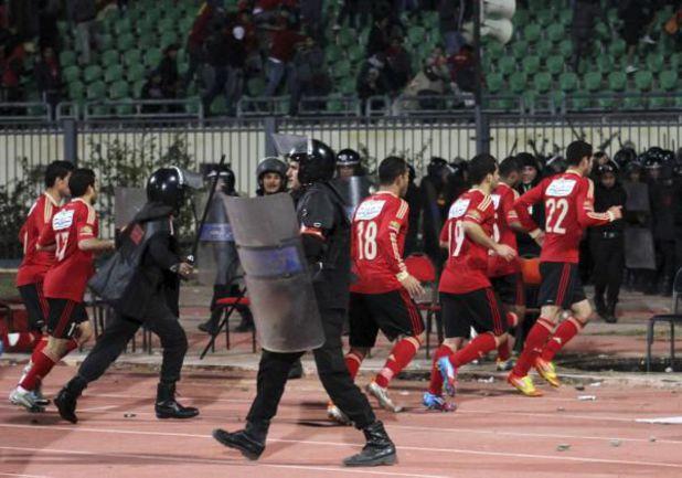 """Футболисты """"Аль-Ахли"""" успевают покинуть поле стадиона в Порт-Саиде под прикрытием спецподразделения полиции. Фото REUTERS"""