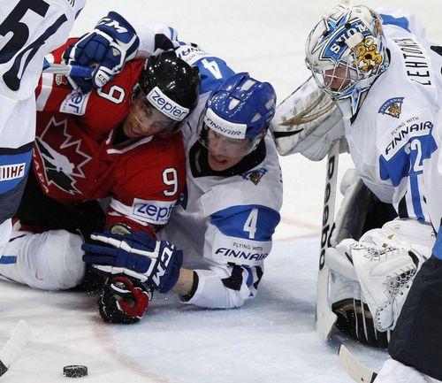 Пятница. Хельсинки. Финляндия - Канада - 3:5. Кари ЛЕХТОНЕН и Осси ВААНАНЕН (№4) останавливают атаку Эвандера КЕЙНА. Фото REUTERS