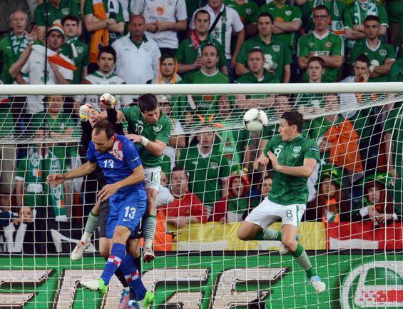 10 июня. Познань. Ирландия - Хорватия - 1:3. Стипе ПЛЕТИКОСА получает удар локтем в челюсть от ирландца Шейна ЛОНГА (№19). Фото AFP