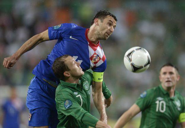 10 июня. Познань. Ирландия - Хорватия - 1:3. Капитан сборной Хорватии Дарио СРНА опережает Эйдена МАКГИДИ. Фото AFP