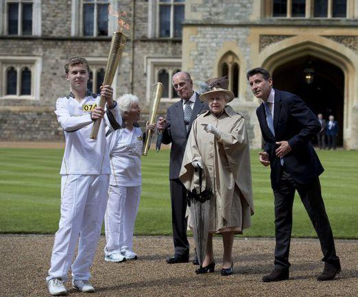 Июль. Лондон. Королева Великобритании ЕЛИЗАВЕТА II и принц ФИЛИПП (в центре) приняли участие в передаче эстафеты олимпийского огня. Фото REUTERS