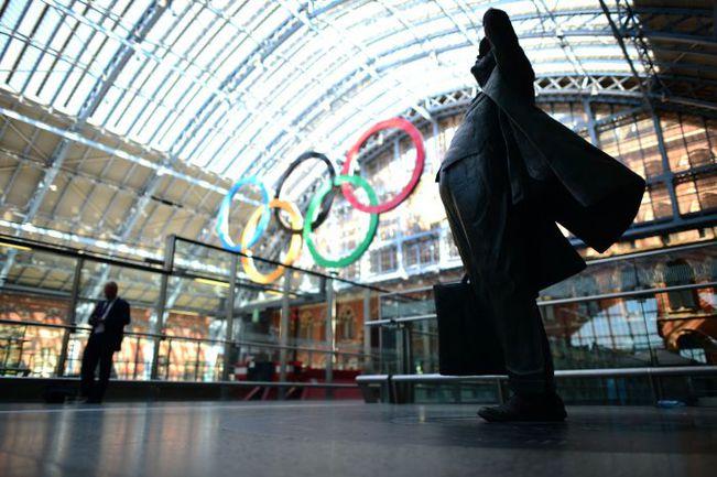 Инсталляция олимпийских колец и статуя изучающего расписание пассажира на лондонском вокзале Сент-Панкрас. Фото AFP