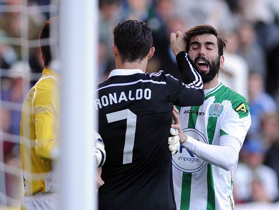 "Суббота. Кордова. ""Кордова"" - ""Реал"" - 1:2. 83-я минута. Нападающий ""Реала"" КРИШТИАНУ РОНАЛДУ мгновениями ранее ударил по ногам Эдимара, нанес удар по лицу Хосе КРЕСПО (справа)... Фото AFP"