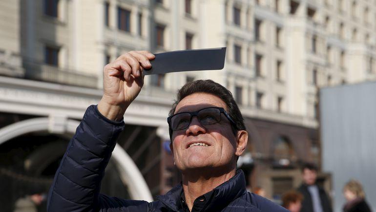 20 марта. Москва. Фабио КАПЕЛЛО смотрит на затмение солнца. Фото Reuters