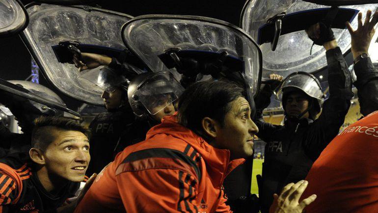 """Четверг. Буэнос-Айрес. """"Бока Хуниорс"""" – """"Ривер Плейт"""". Игроки """"Ривер Плейт"""" покидают поле под защитой полиции. Фото AFP"""