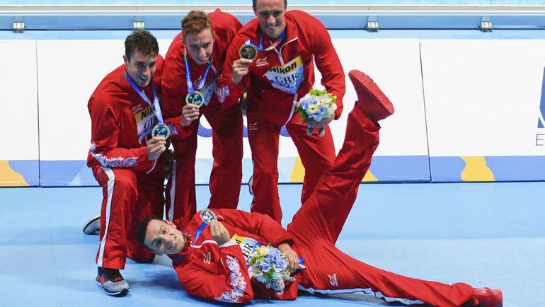 Джеймс ГАЙ (лежит) вместе с партнерами по золотой эстафетной команде. Фото REUTERS