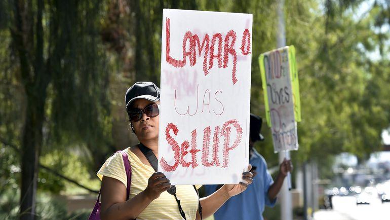 Женщина с плакатом перед больницей, в которой находится Ламар Одом. Фото REUTERS