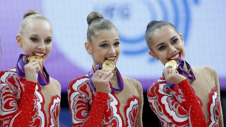 Яна КУДРЯВЦЕВА (слева), Александра СОЛДАТОВА (в центре) и Маргарита МАМУН с золотыми медалями чемпионата Европы. Фото AFP