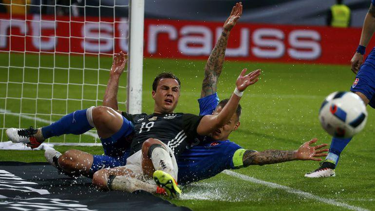 Сегодня. Аугсбург. Германия - Словакия - 1:3. Мартин ШКРТЕЛ в подкате против Марио ГЕТЦЕ. Фото Reuters