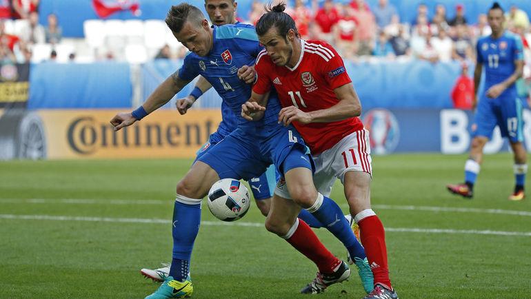 Сегодня. Бордо. Уэльс - Словакия - 2:1. Ян ДЮРИЦА (№4) и автор первого гола Гарет БЭЙЛ. Фото Reuters
