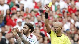 Сергей КАРАСЕВ показывает карточку защитнику сборной Венгрии Тамашу КАДАРУ.