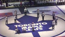 """Члены Зала славы """"Торонто"""" стоят на клубном логотопе во время торжественной церемонии."""