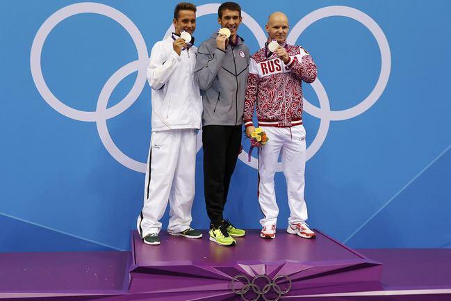 Пятница. Лондон. Чад ЛЕ КЛОС (слева), Майкл ФЕЛПС (в центре), Евгений КОРОТЫШКИН (справа) на олимпийском пьедестале почета. Фото REUTERS Фото REUTERS