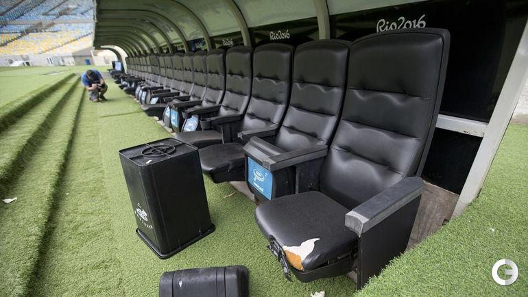 Перевернутый мусорный ящик лежит у кресел, предназначенных для футболистов и тренеров.
