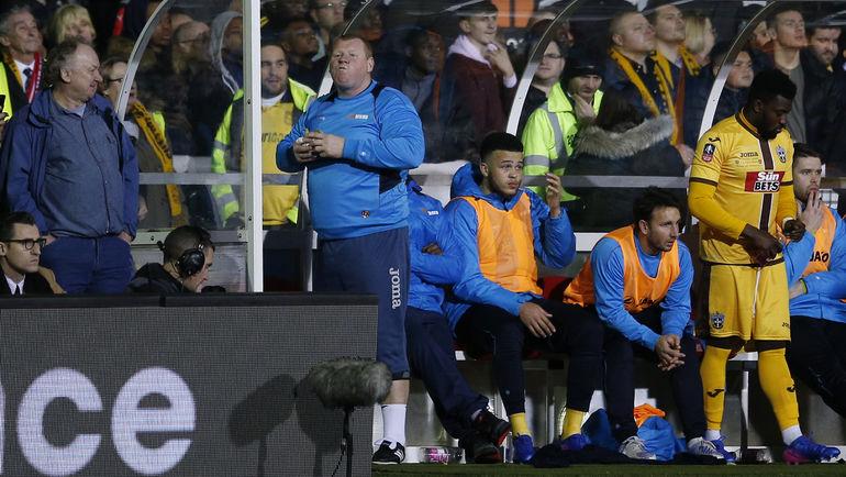 """Понедельник. Саттон. """"Саттон Юнайтед"""" - """"Арсенал"""" - 0:2. Ставший знаменитым вратарь """"Саттона"""" Уэйн ШОУ перекусывает пирогом по ходу матча. Фото Reuters"""