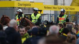 Вторник. Дортмунд. Болельщики покидают стадион под присмотром полиции.
